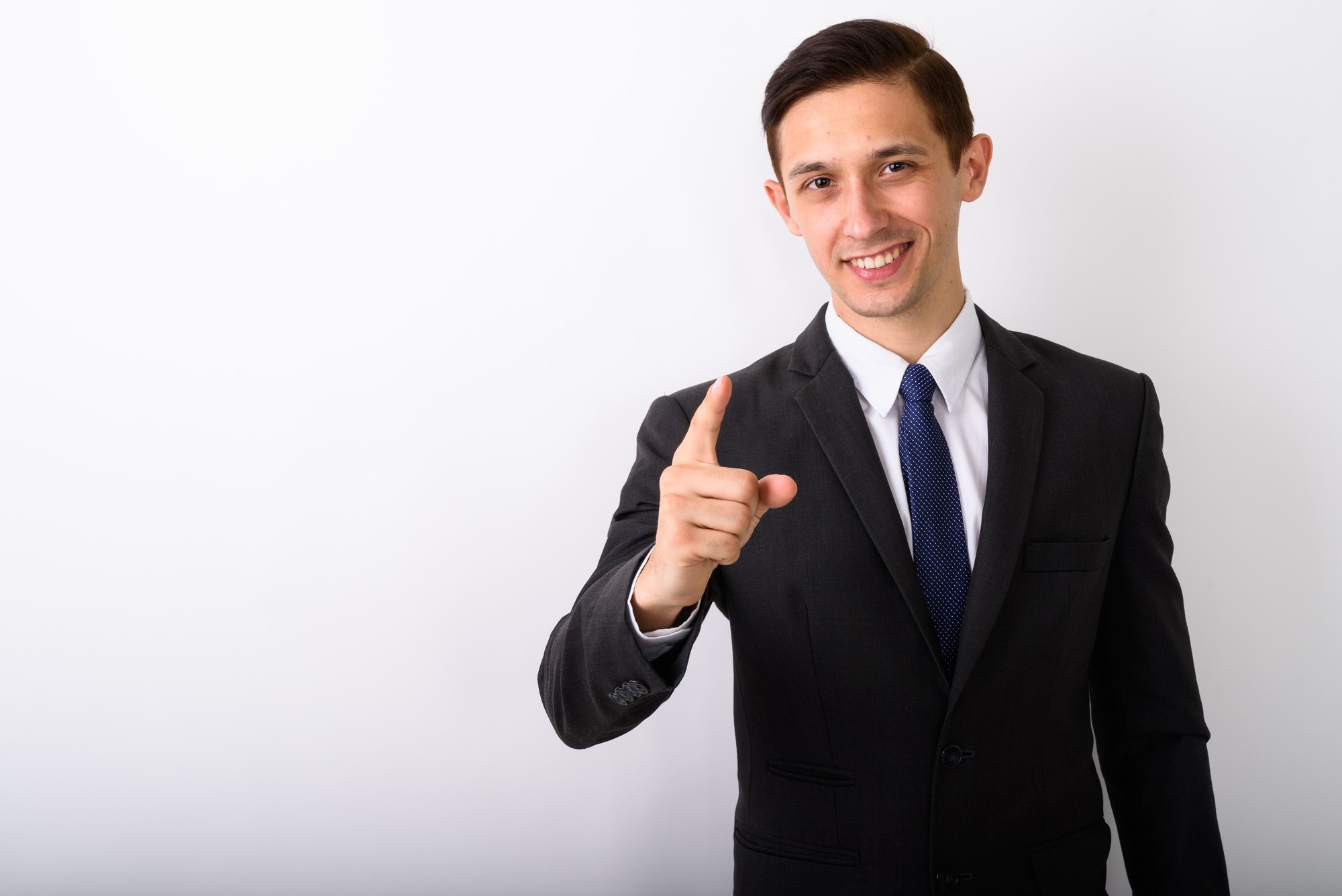 Studio shot of young happy businessman smiling while pointing fi